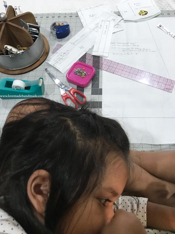 Toddler Nursing while mom drafts a sewing pattern - Lovemade Handmade